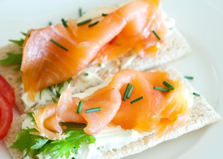 Smoked salmon on crackers with cream cheese and sprinkled with dill